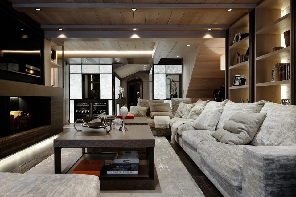 A sleek, modern living room with grey furniture and wood paneling and floor to ceiling windows revealing the snow outside.