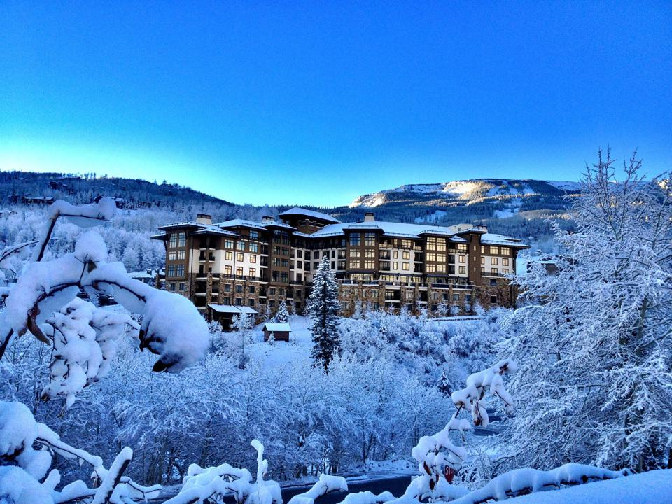 A low rise resort surrounded by snowy mountains