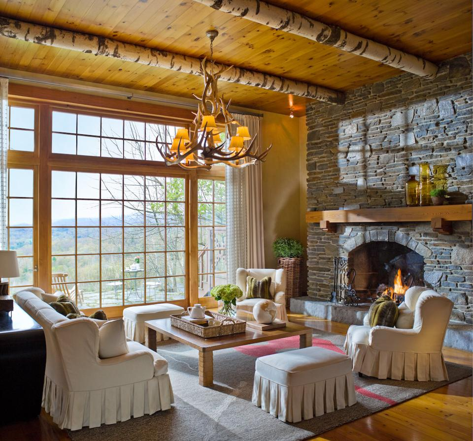 A high ceilinged room with floor to ceiling windows, raw wood beams, a stone fireplace and cozy furniture.