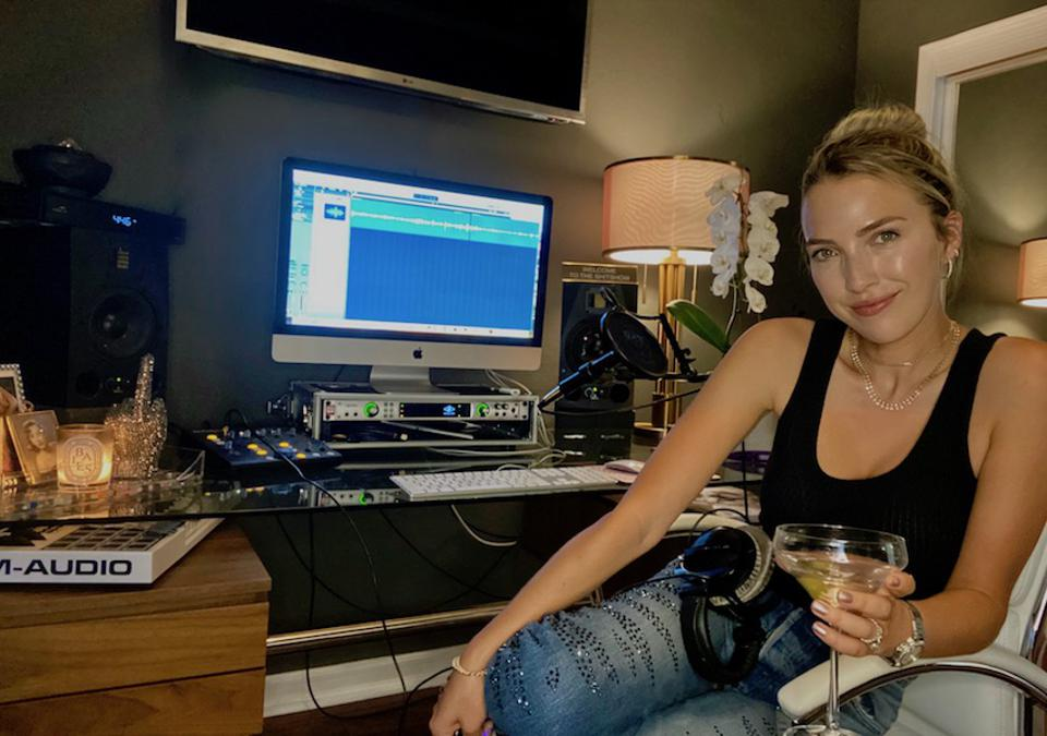 Jackie Schimmel holds a martini and sits in her podcast studio