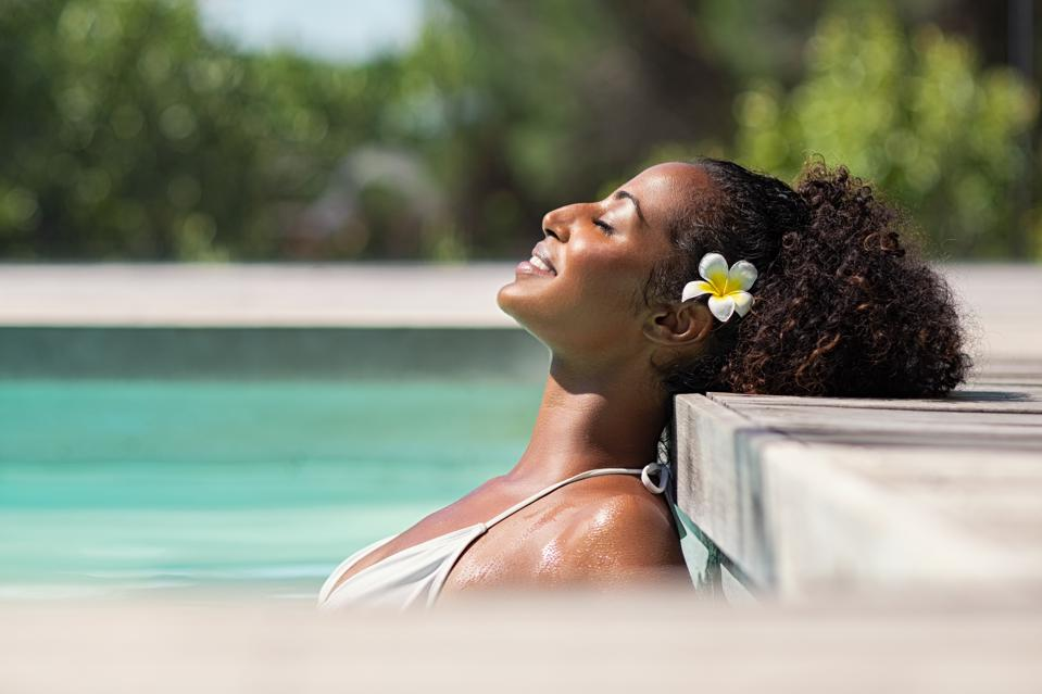 Beautiful african woman in pool relaxing