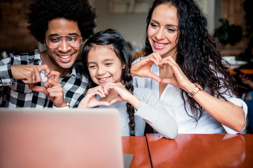 Happy multiethnic family having fun while using laptop together, video chat concept