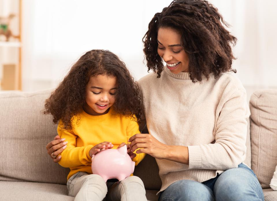Cheerful Mother Teaching Daughter How To Save Money At Home