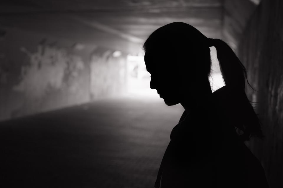 Depressed Young Female Standing in a Dark Tunnel