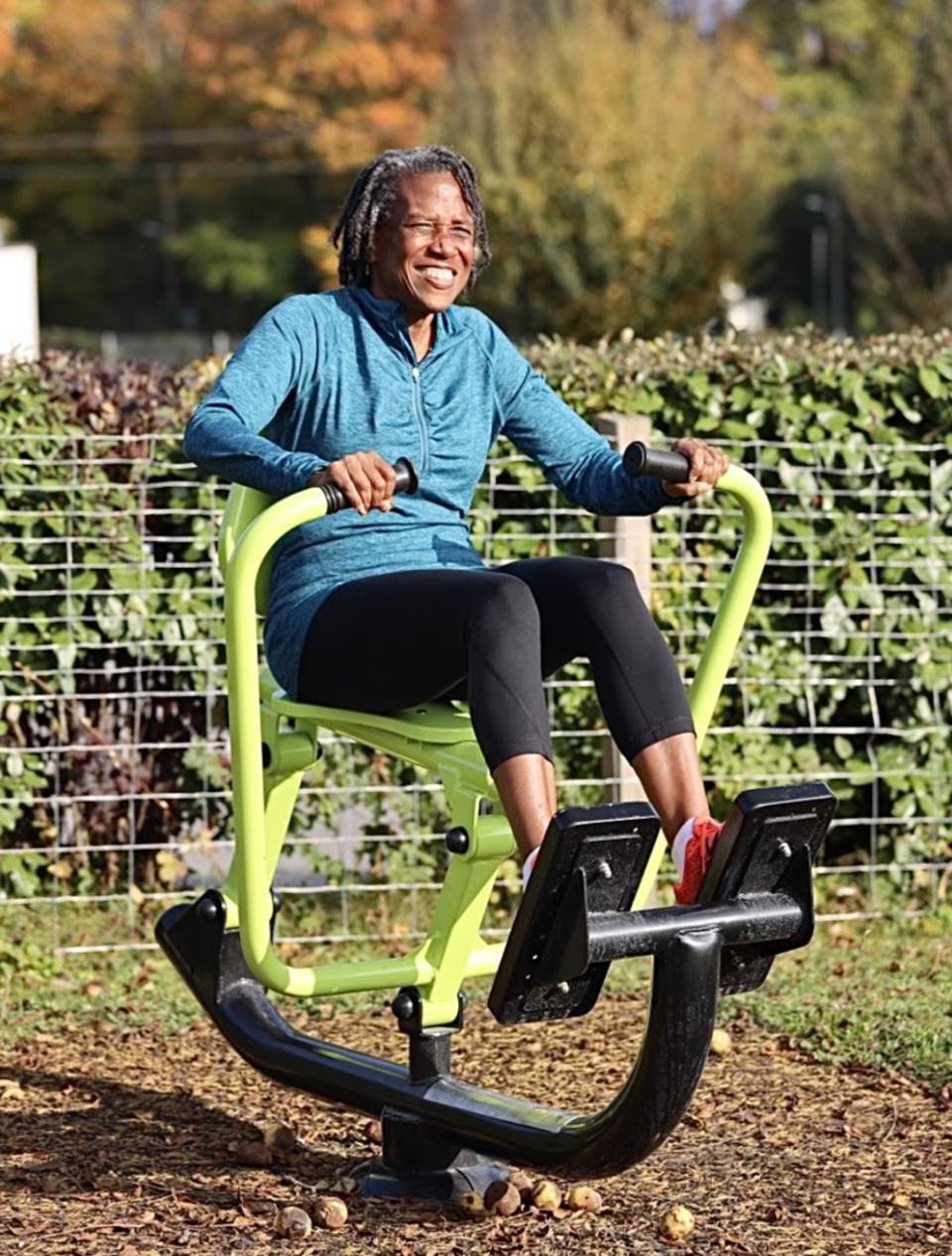 A Black woman works out on exercise equipment outside.