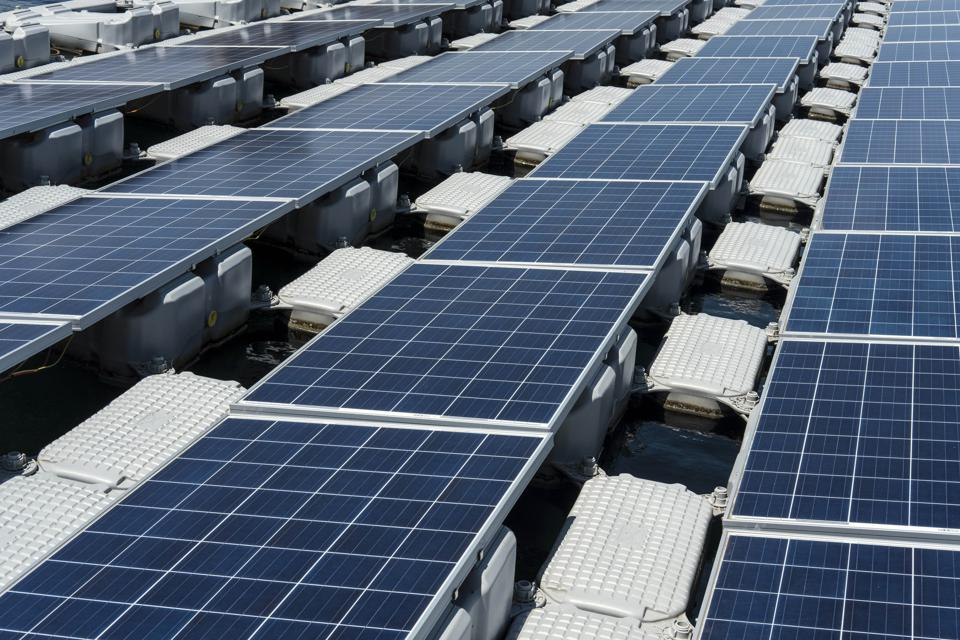Solar panels containing photovoltaic cells float on water at a hydro electric dam. Photographer: Daniel Rodrigues/Bloomberg