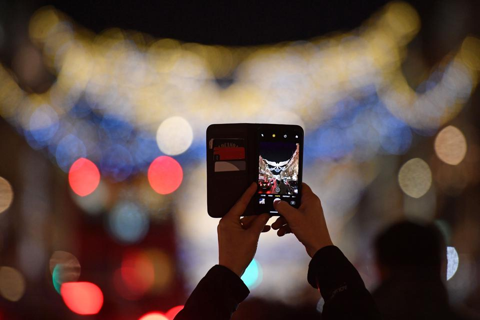 Shopper takes a photo of Christmas Lights on London's Regent Street