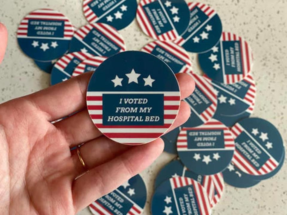 A pile of a red, white and blue patriotic pins that say ″I VOTED FROM MY HOSPITAL BED.″