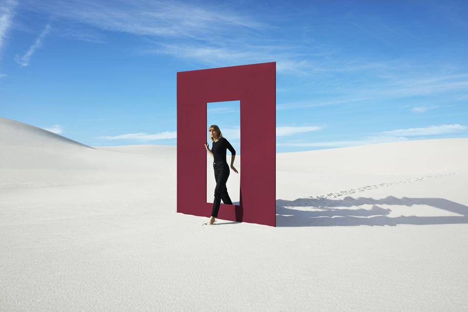 Young fashion model walking through red door frame at desert against sky