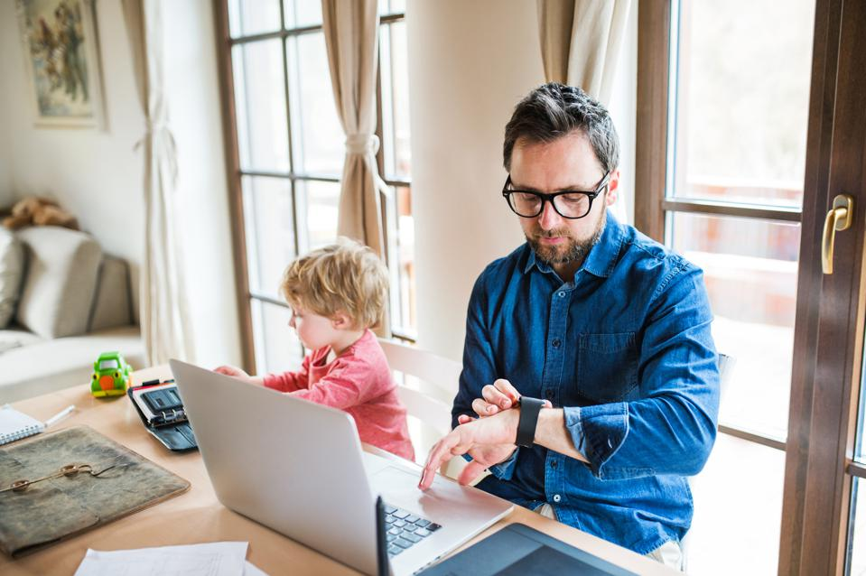 Mature man with toddler boy working at home office, using laptop and smartwatch.