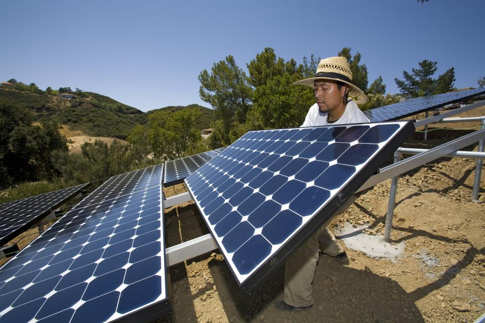 Green workers install a residential grid-tied solar array on a hillside in Malibu, California, USA.