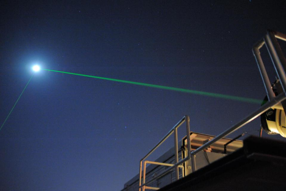 Color photo of a green laser beam shooting into the night sky.