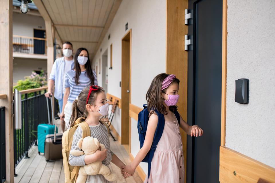 Family with children and face masks outdoors by hotel in summer, holiday concept.