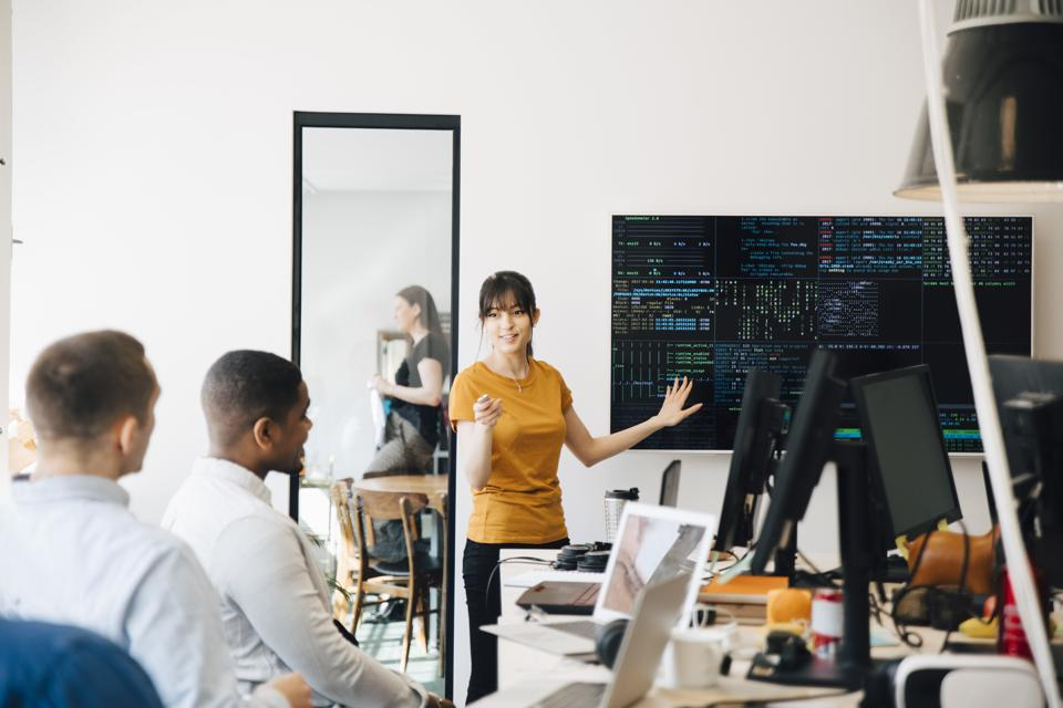 Female hacker interacting with colleagues while giving presentation in office