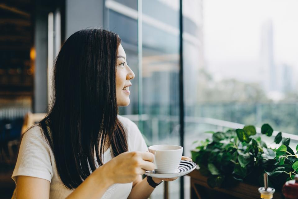 Smiling young woman holding a cup of coffee looking through window in a restaurant