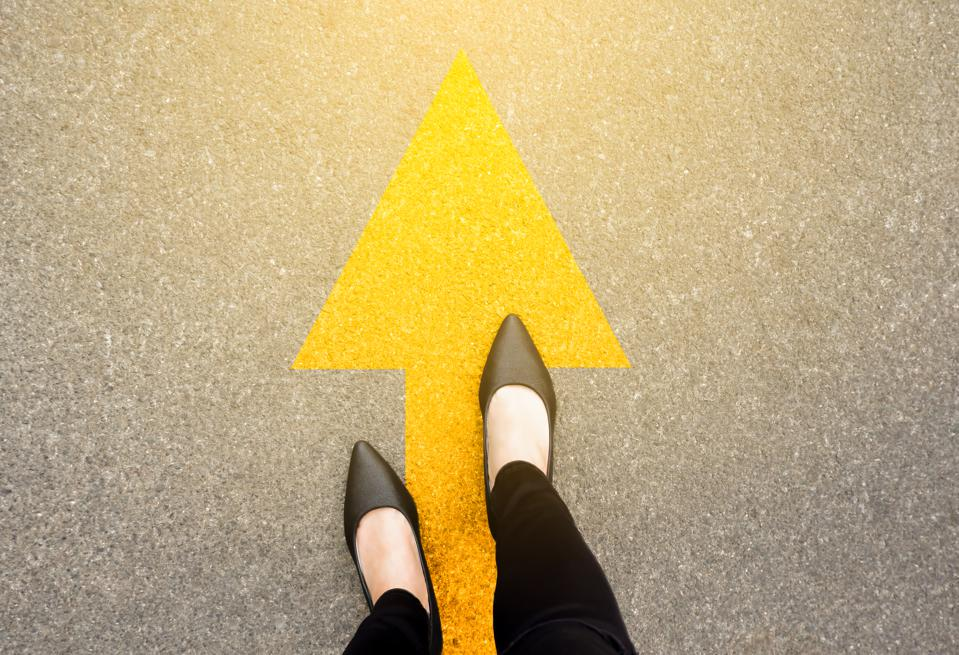 Feet and arrows on road background in starting line beginning idea. Top view. Business woman in black shoes on pathway with yellow direction arrow symbol. Moving forward, new start and success.