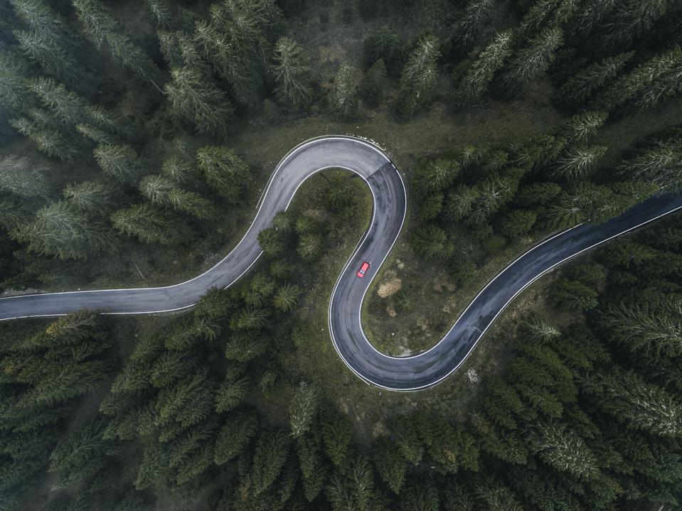 Winding forest road and one car