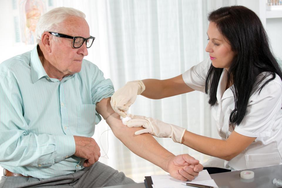 A female lab technician prepares an older man for having blood drawn
