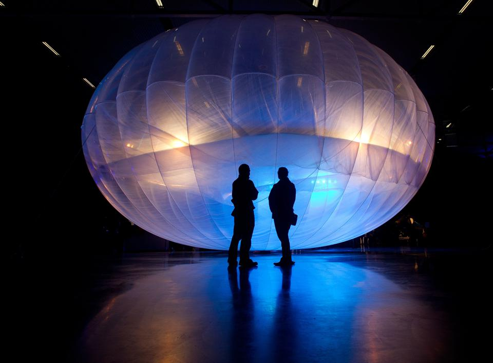 Visitors stand next to a high altitude WiFi internet hub, a Google Project Loon balloon.