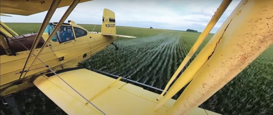 Ag pilot Scott Palmer sprays fungicide on an Iowa corn field.
