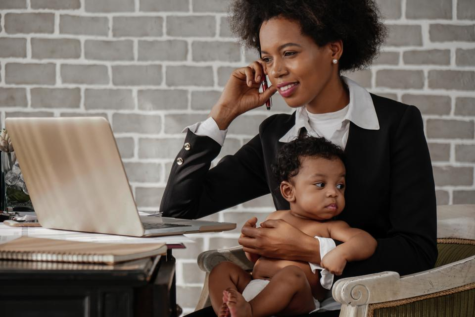 Black business woman taking care of her baby boy while working at home.