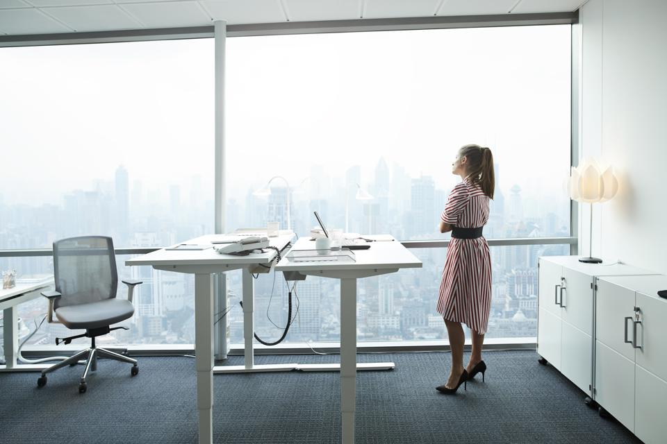 Businesswoman standing in modern office and looking out of big windows at beautiful skyline