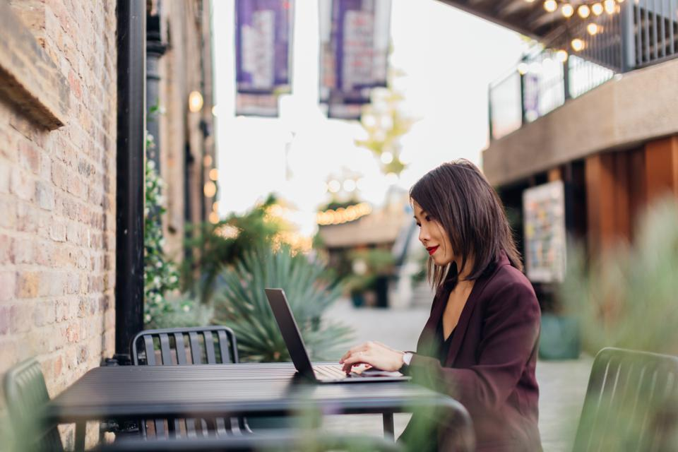 Young successful female freelancer working at an industrial style outdoor cafe