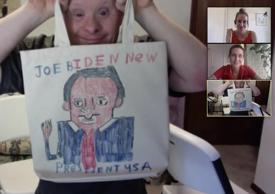 A man with Down Syndrome holds up a tote bag where he drew a picture of Joe Biden.