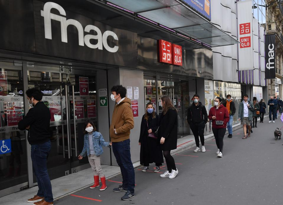 People wearing protective face masks in front of a Fnac store on May 11, 2020 in Paris,