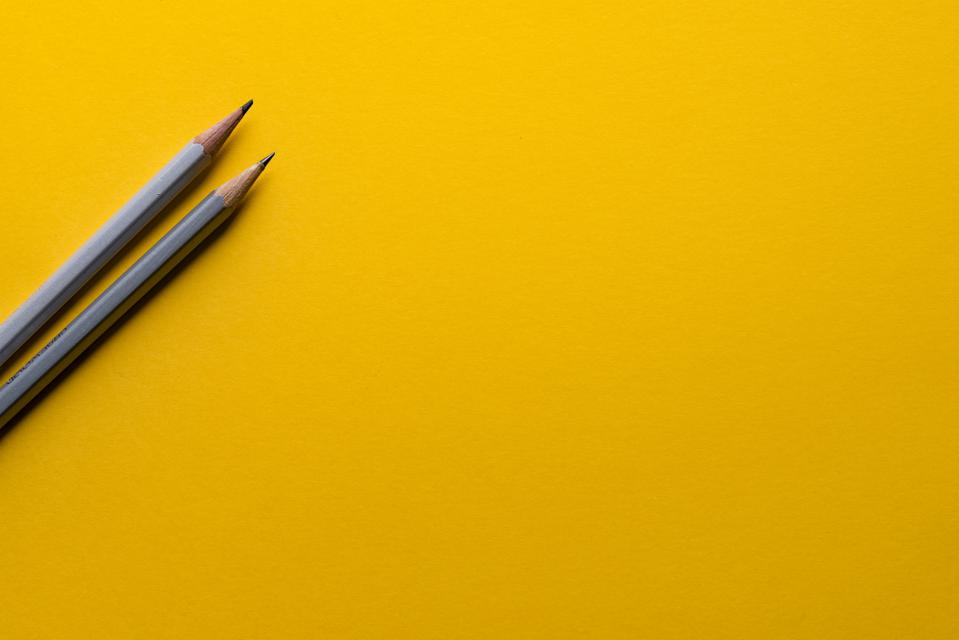 A blank gold sheet of paper with two sharp pencils resting on it.