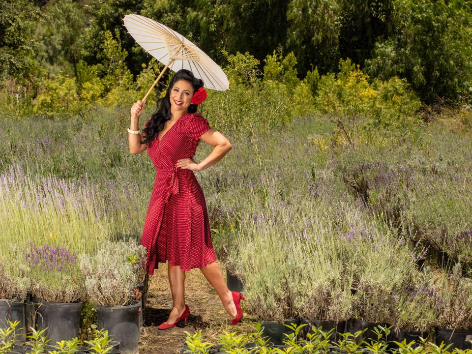 Padilla in a red dress, heels and flower in hair with white umbrella.