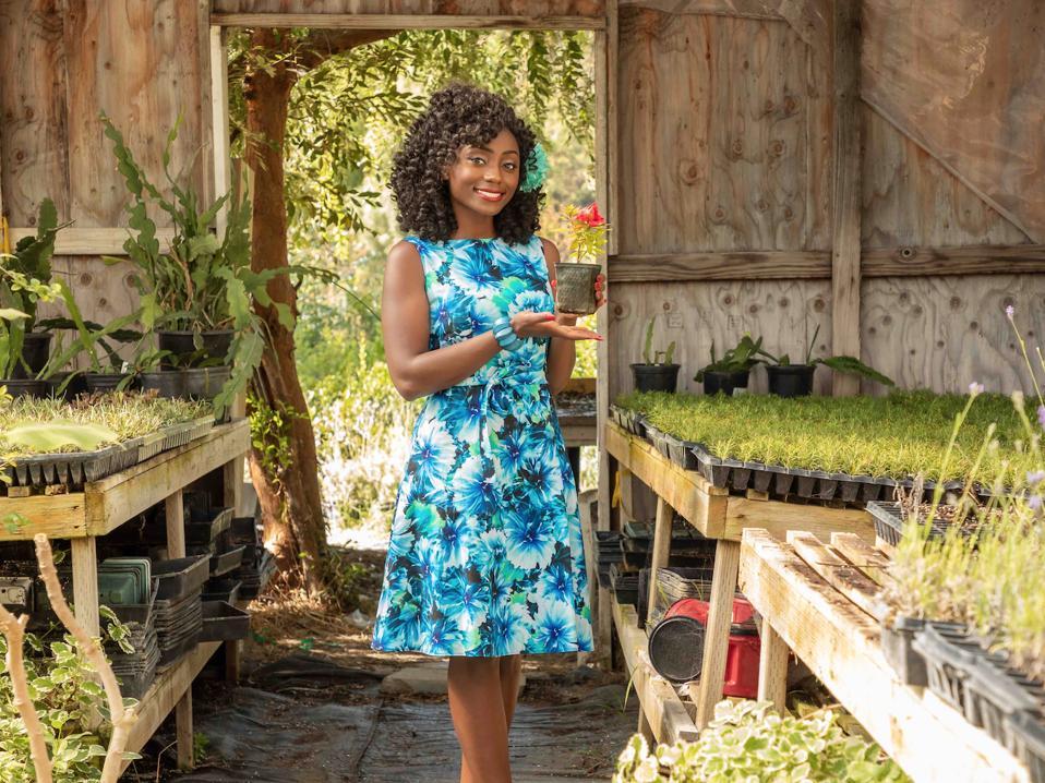 Ahmika poses in a blue dress holding a flower pot.