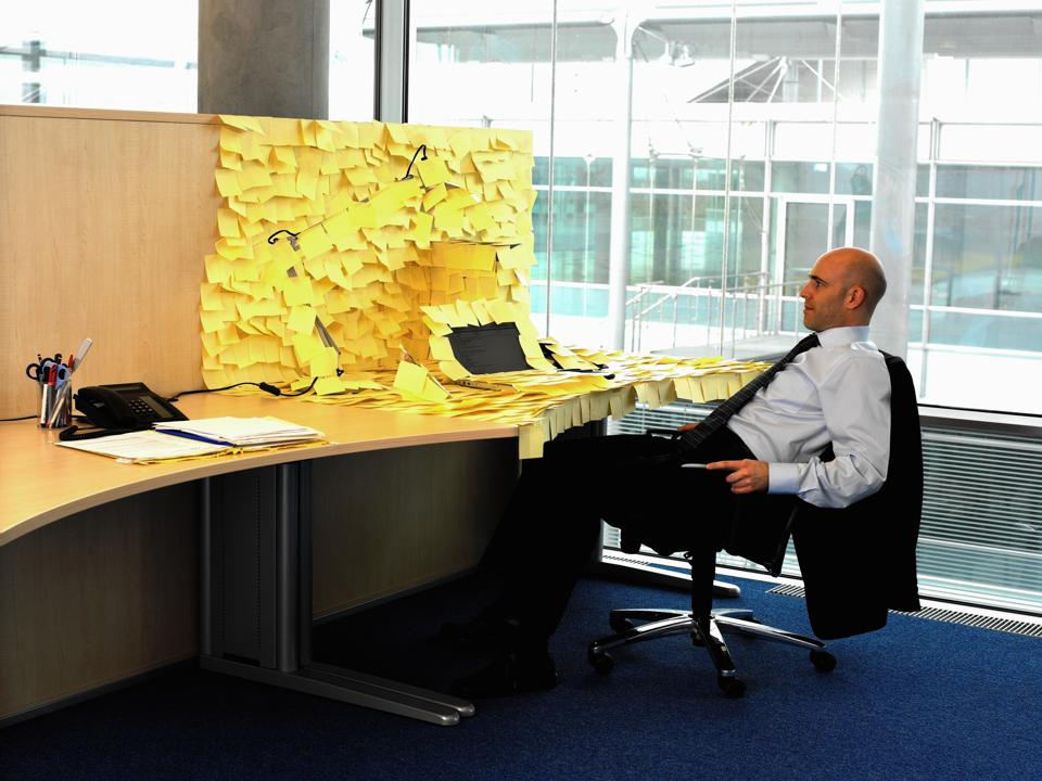 Man sitting at desk covered in yellow memo notes