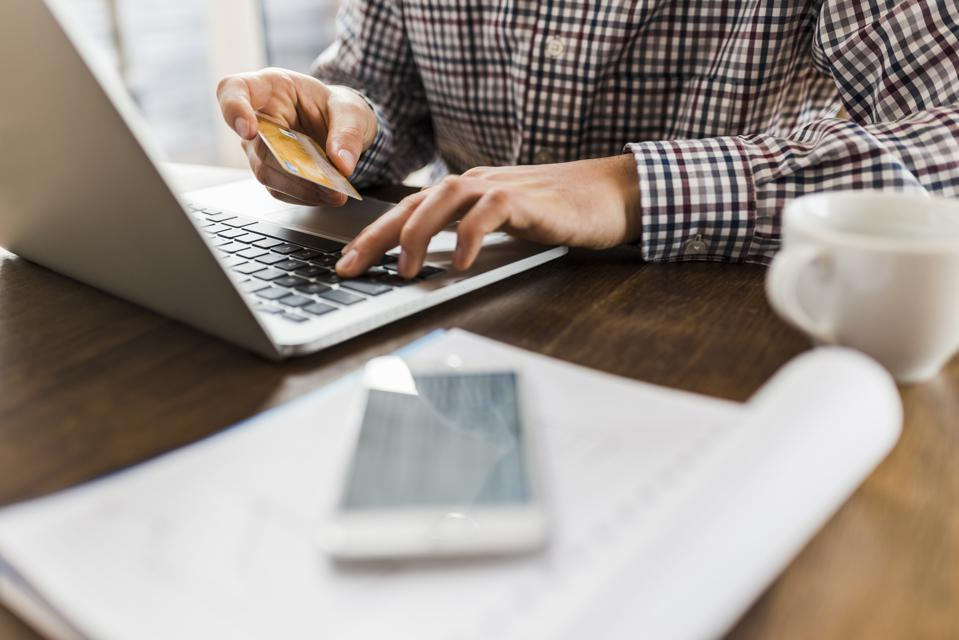 Close-up of man using laptop and holding credit card