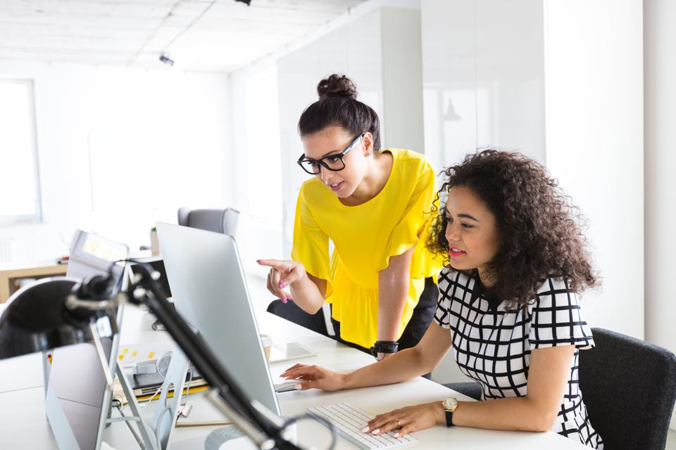 Creative professionals working together on computer