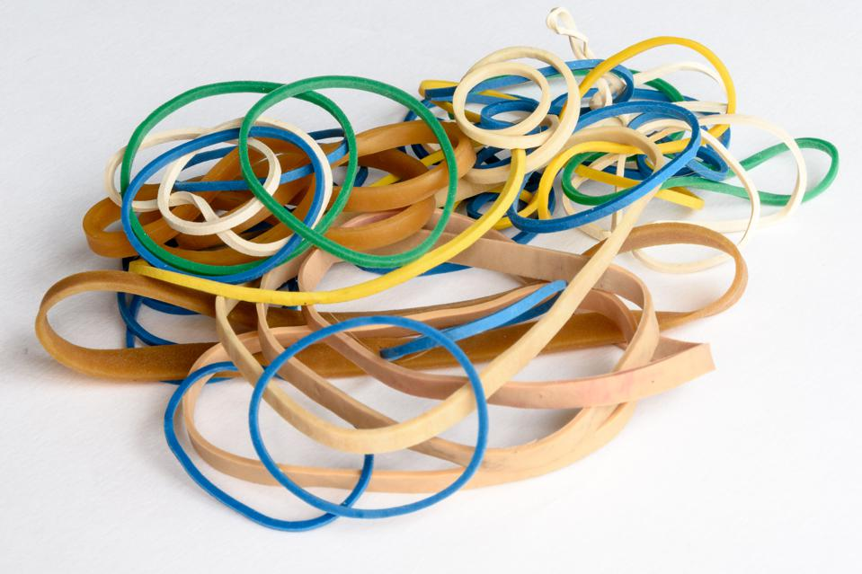 Close-Up Of Colorful Rubber Bands Over White Background