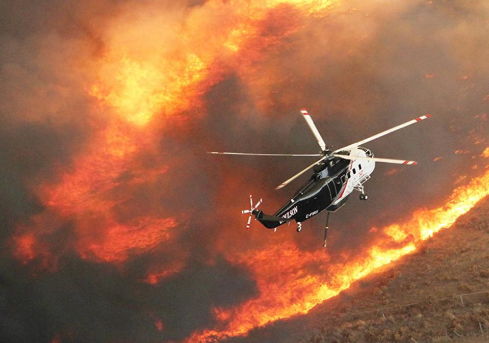 A Coulson Sikorsky S1 positions for a fire retardant drop over a ridgeline.