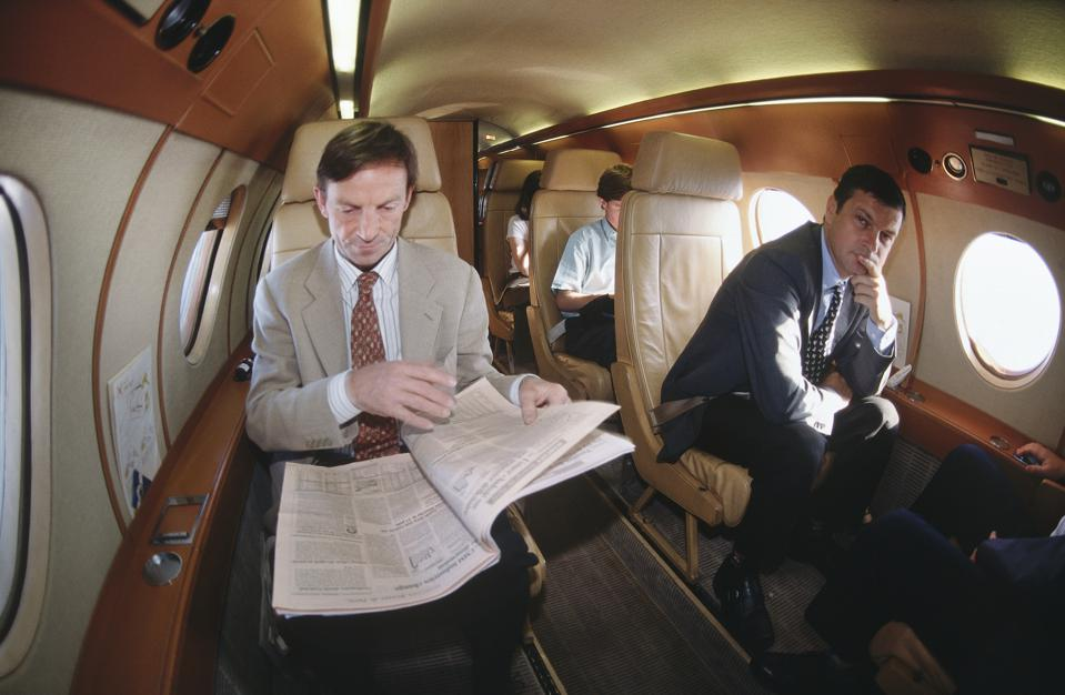 businessmen and women sitting in the passenger cabin of a Dassault Falcon 20