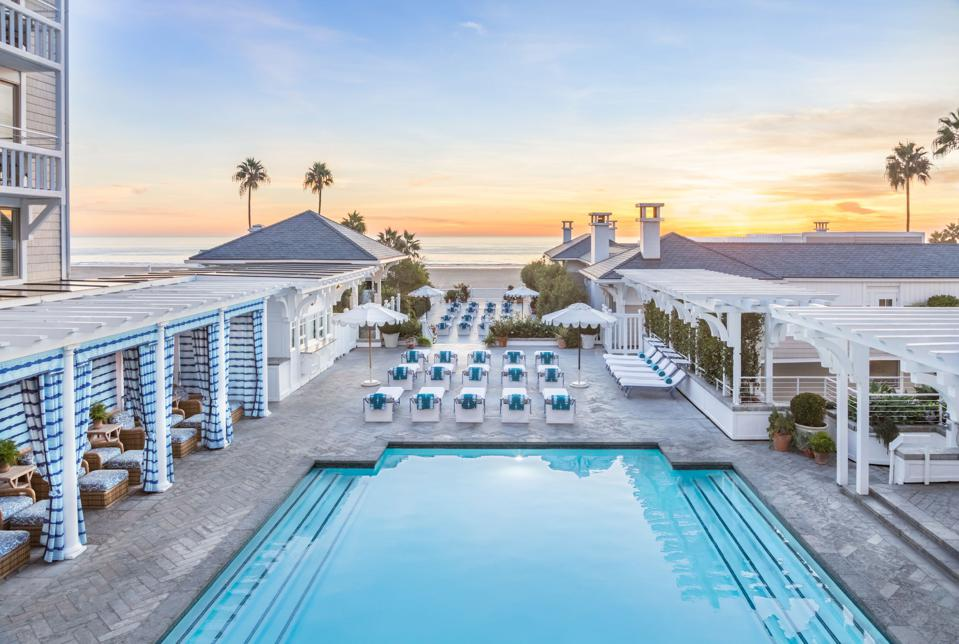 large pool near the beach with surrounding deck chairs