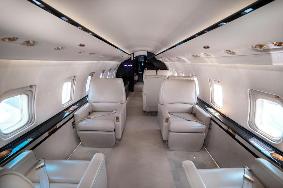 The inside of a private jet with spacious seating.