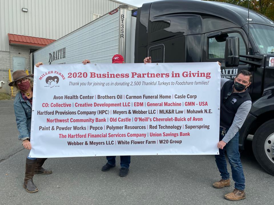 The team at Miller Farms holds up a thank-you poster listing its 2020 Business Partners in Giving.