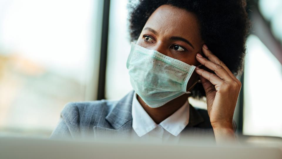 Worried African American businesswoman with protective mask thinking of something in the office.