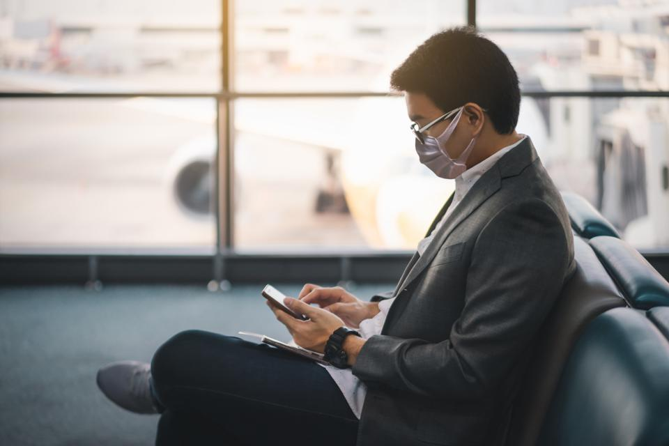 Young asian businessman wearing protective face mask sitting and using smartphone at waiting area in international airport due to Coronavirus disease or COVID-19 outbreak situation in all of world.