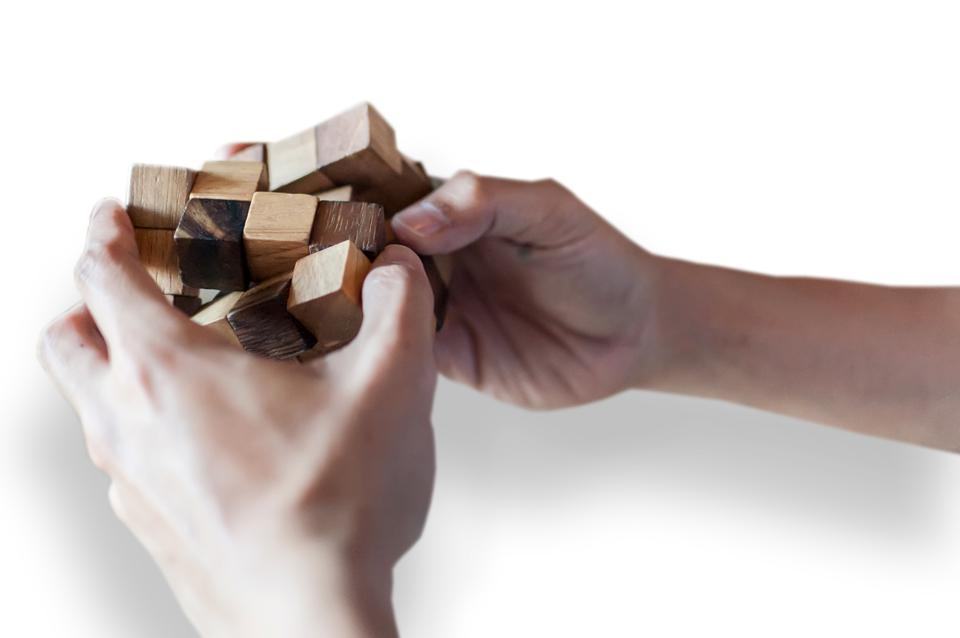 Close-Up Of Hand Holding Puzzle Cube Over White Background