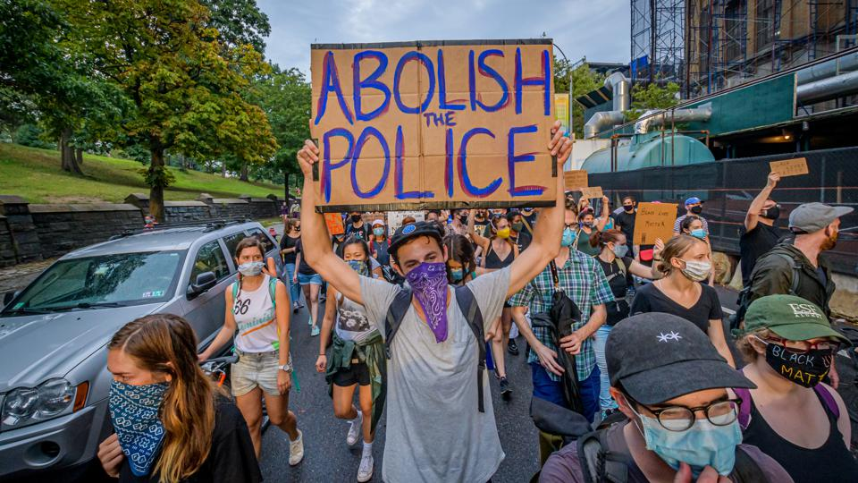 A participant holding a Abolish Police sign at the protest.