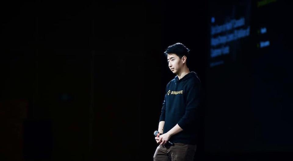 Young Asian entrepreneur giving TED style talk on stage against black background