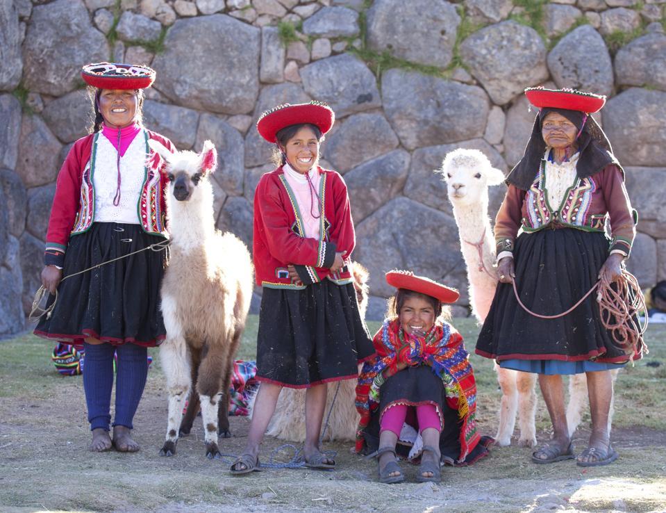 Traditionally dressed Peruvian women with alpacas, Cusco, Peru.