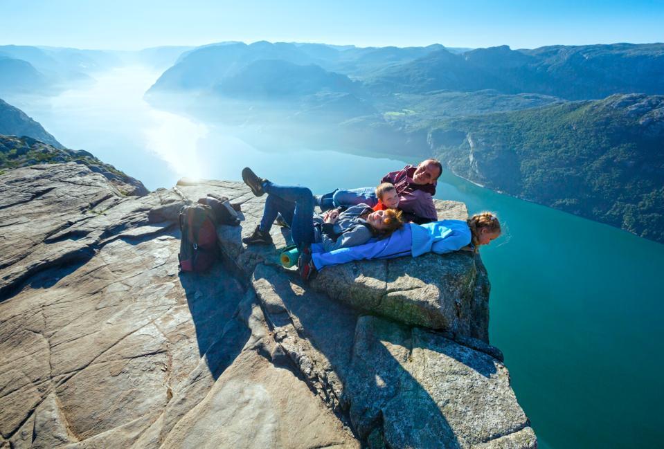 Happy American family on top of Preikestolen cliff in western Norway.