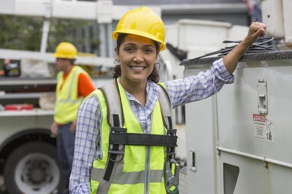 A female utilities engineer wearing a high-viz tabard and hard-hat.