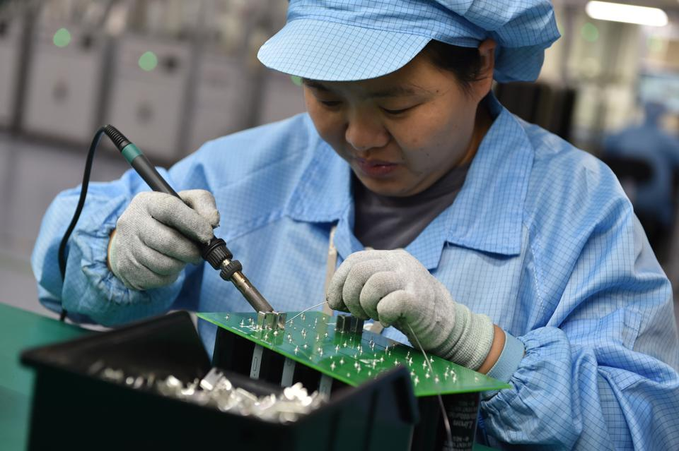 A worker does a manual hand-solder step in the production of a circuit board in China's Jiangsu Province.
